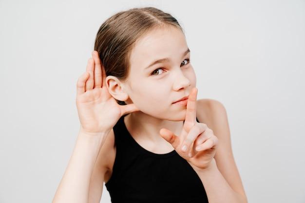 黒のtシャツを着た10代の少女が、耳に手をかざして耳を傾けます。