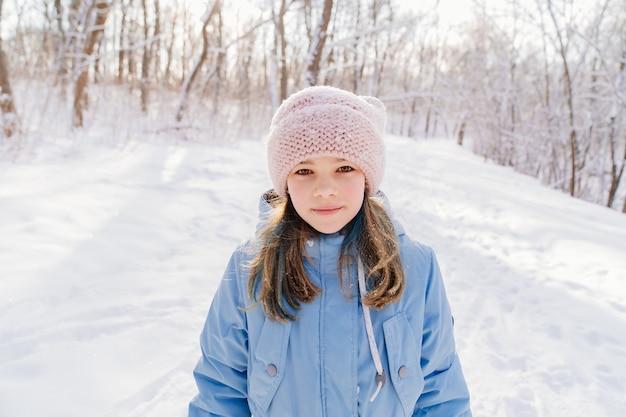 Девушка в синем пальто и розовой шляпе стоит в заснеженном лесу.