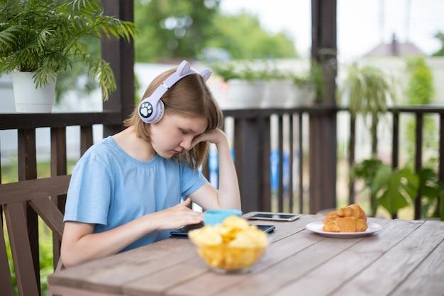 タブレットスマートフォンとヘッドフォンで青いtシャツを着た10代の少女は、夏のカフェの木製のテーブルに座って、ソーシャルネットワークで通信し、音楽を聴きます
