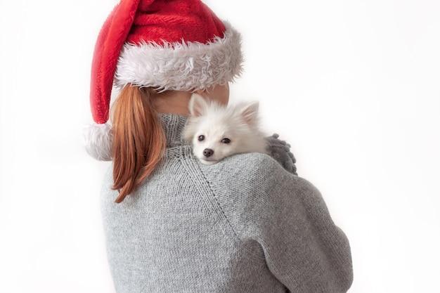 강아지와 함께 산타 모자에있는 십 대 소녀