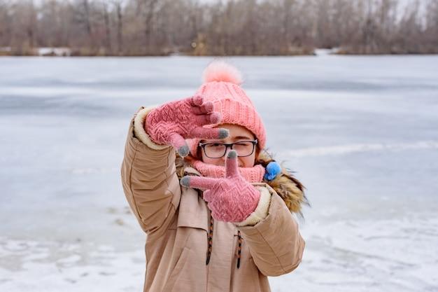 그녀의 손가락으로 프레임 제스처를 하 고 장갑에 십 대 소녀. 얼어 붙은 강 소녀
