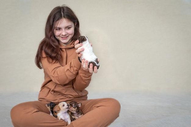 10代の少女が小さな子犬と一緒に床に座って、彼女の手で1つを持っています