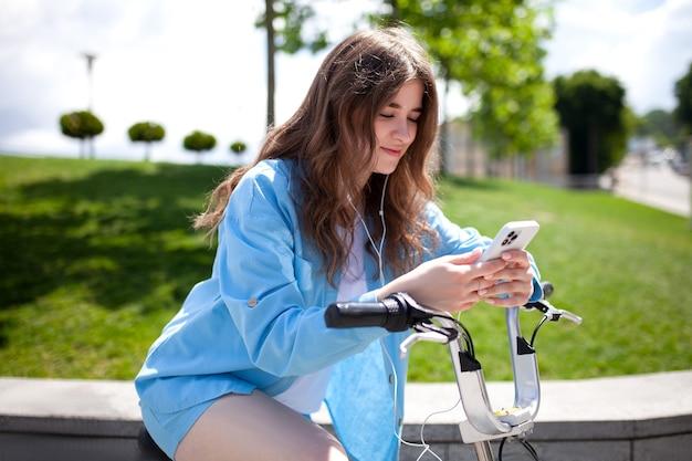 10대 소녀가 헤드폰을 귀에 꽂고 친구들과 문자 메시지를 주고 있다