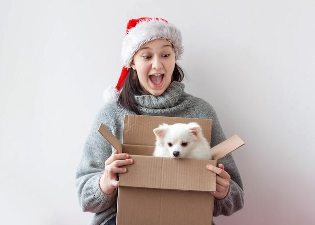 10代の少女が段ボール箱を開けると、小さなポメラニアン犬がいます。