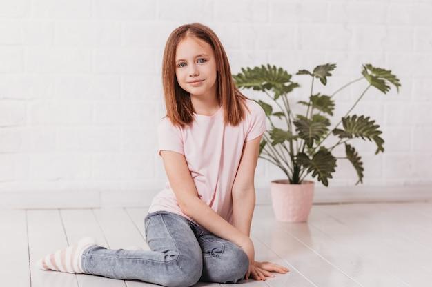 Девушка-подросток сидит на полу в белой комнате и смотрит в камеру
