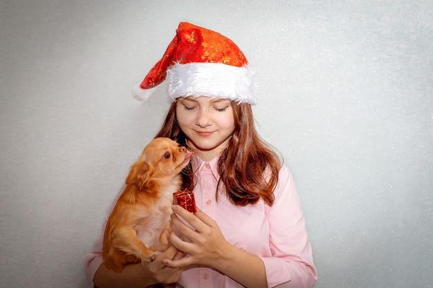 Девочка-подросток стоит в шляпе санты, держит рыжую собаку чихуахуа и предлагает ей подарок.