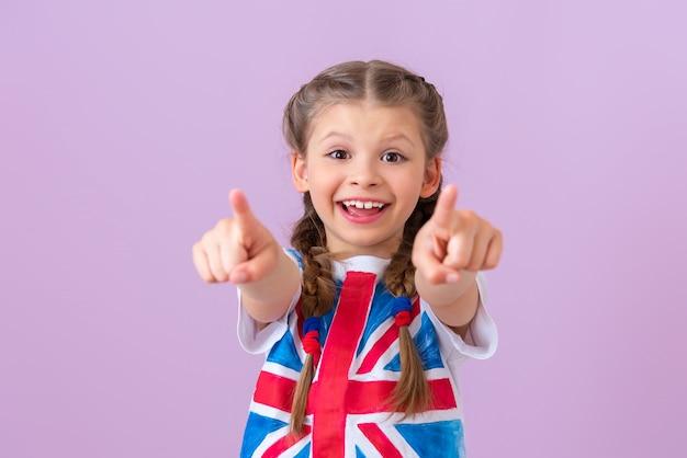 Девушка-подросток с английским флагом показывает пальцами вперед.