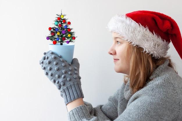 灰色のミトンと赤と白のサンタの帽子のブロンドの髪を持つ10代の少女は、小さな青い植木鉢を持っています
