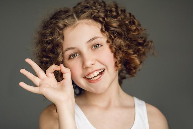 巻き毛の10代の少女は、指に「すべてが大丈夫です」というシンボルを表示します。