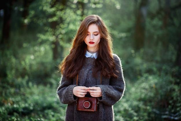 Девушка-подросток с длинными темными волосами и ярко-красными губами в теплом шерстяном свитере со старым пленочным фотоаппаратом в кожаном футляре, висящем на шее, стоит на фоне леса на закате.