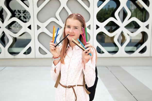 그녀의 손에 연필을 들고 분홍색 머리를 가진 10대 소녀는 도시의 예술 공간, 행복한 10대의 초상화에서 행복합니다