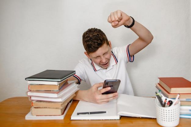 Подросток дома за учебником смотрит в смартфон и видит радостную новость
