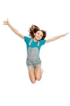 デニムのオーバーオールと青いタンクトップの10代の女の子が感情的にジャンプします。 。垂直。