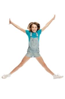 데님 바지와 파란색 탱크 탑의 십대 소녀가 감정적으로 뛰어 오른다. . 세로.