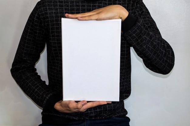 市松模様のジャケットを着たティーンエイジャーは、広告用の白い長方形を持っています