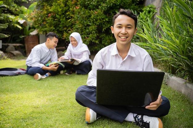 制服を着た10代の若者が、友達とおしゃべりしながらノートパソコンを使って微笑む