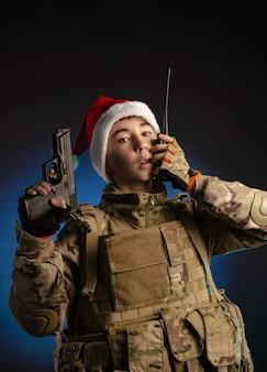 군인 제복을 입고 산타클로스 모자를 쓴 십대가 라디오에서 이야기하고 있다