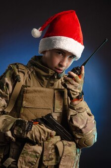 군인 제복을 입고 산타클로스 모자를 쓴 십대가 라디오에서 이야기하고 있다 프리미엄 사진