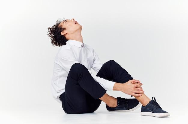 スーツとスニーカーのティーンエイジャーは、明るい部屋の側面図で床に座っています