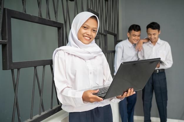 ノートパソコンを使用している間、ベールと制服を着た10代の若者がカメラに微笑んだ