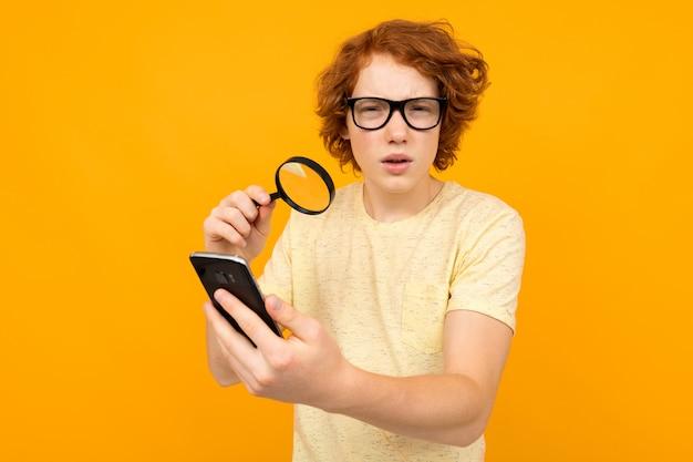 拡大鏡を手に持つメガネのティーンエイジャーは、黄色の背景に彼の手でスマートフォンを見てください。新しいビジョンのコンセプト