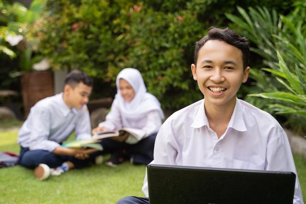 芝生の上に座っているラップトップを使用しながら、制服を着た10代の若者が微笑む