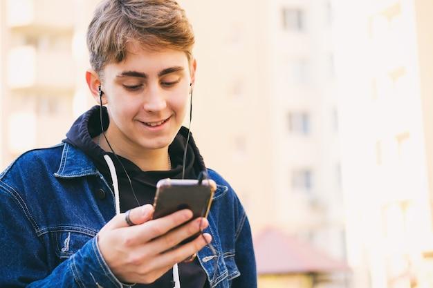 헤드폰을 든 도시의 십대가 전화로 음악을 듣는다-도시를 걷는 동안 젊은 남자가 스마트 폰으로 문자 메시지를 읽는다