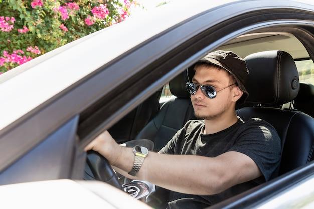 10代の若者が、ひげを生やしたファッショナブルなサングラスをかけた現代の若い男を運転していて、白い車を運転しています...