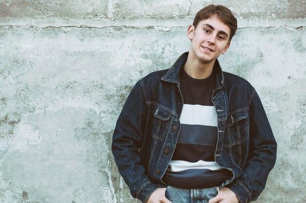 Подросток стоит у серой бетонной стены - молодой человек улыбается и смотрит в камеру