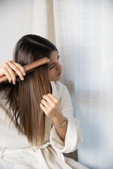 Подросток выпрямляет волосы утюжком для волос в белом халате