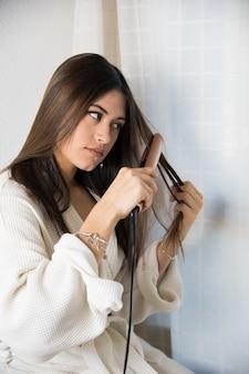 Подросток выпрямляет волосы утюжком