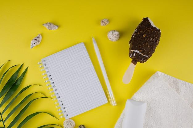 휴가 계획, 조개 껍질, 초콜릿 코팅 아이스크림, 흰색 수건, 자외선 차단제 또는 자외선 차단제 튜브 및 복사할 장소가 있는 현대적인 노란색 배경에 녹색 야자수 잎을 위한 템플릿.