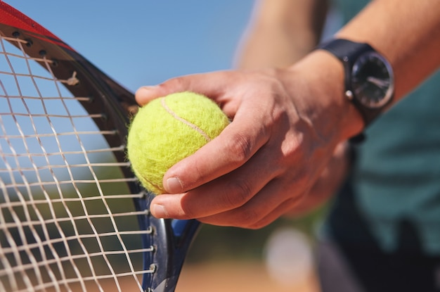 ラケットとボールを手に持っているテニスプレーヤー