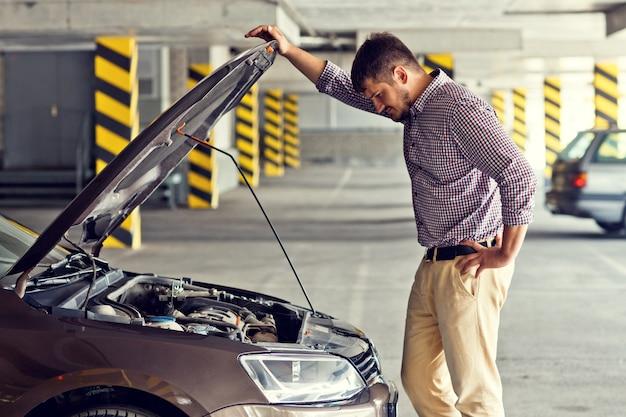 긴장하고 좌절 한 청년 운전자가 부서진 차 옆에 서서 주차장의 후드 아래를 봅니다.