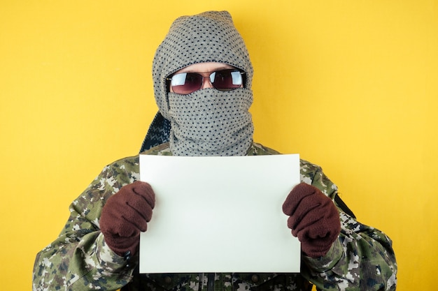 カモフラージュ、眼鏡、マスクを身に着けたテロリストの男が一枚の紙を持っています。匿名性とテロリズムの概念は条件を要求します