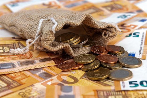 Текстильный мешок, наполненный монетами на поверхности банкнот евро, крупным планом