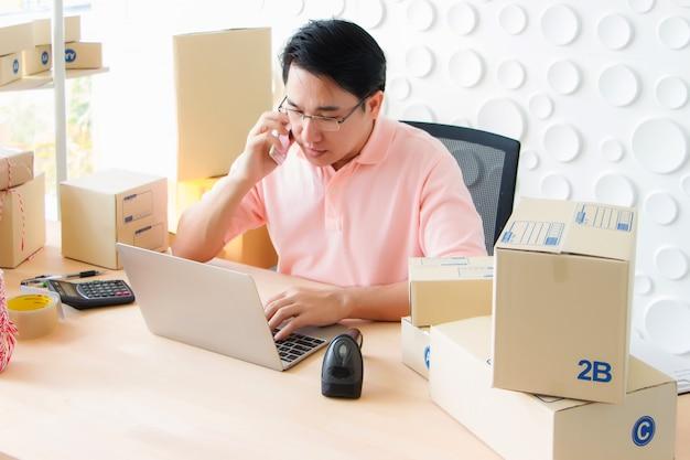 タイのアジア人男性が電話でノートを机の上に置き、オフィスにバーコードスキャナーと計算機を置いています。
