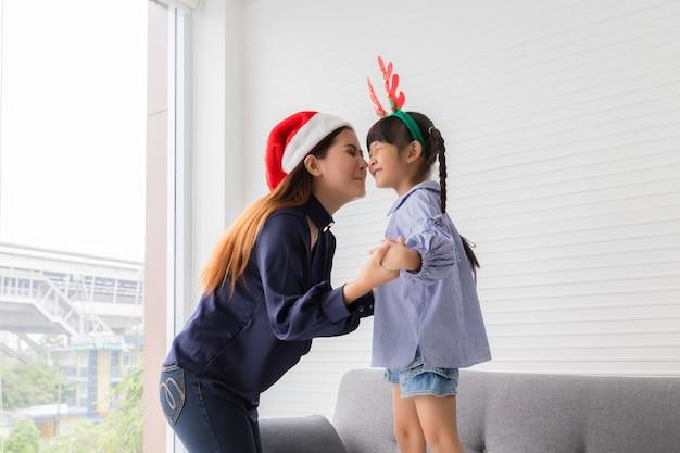 赤いサンタクロースの帽子をかぶっているタイのアジアの女性が、娘の頬にキスしようとしています。彼らは自宅のリビングルームで笑顔と幸せです。クリスマスを祝うというコンセプトで