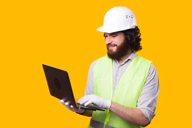 감사하는 젊은 건축가가 컴퓨터를 들고 메시지를 입력하는 것은 노란색 벽 근처에 서 있습니다