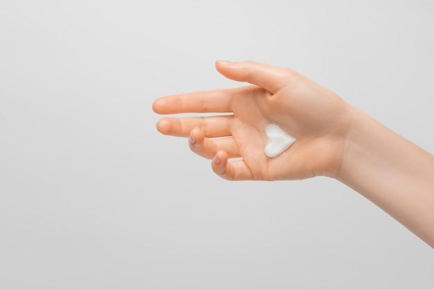 女性の手に濃厚なハート型のクリーム。手入れの行き届いた手、自然な短い爪、明るい背景。