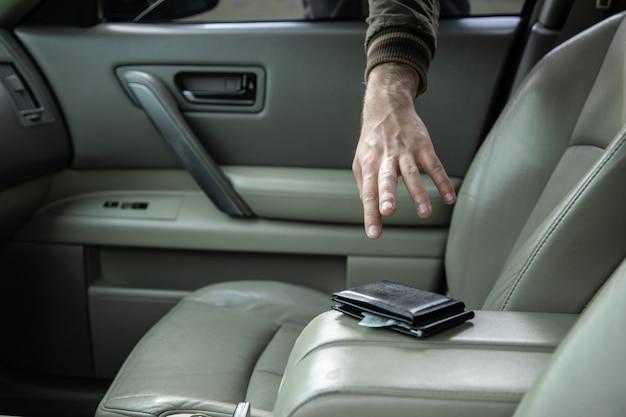 銃を持った泥棒が車から財布を盗む