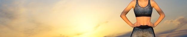 Худенькая спортивная девушка делает перерыв между занятиями на фоне красивого неба на закате