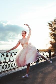 Худенькая балерина в розовом шелковом платье-корсете изящно приподнимает заостренную ногу на берегу реки ...