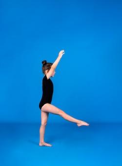 얇은 작은 체조 선수는 텍스트를 위한 장소가 있는 파란색 배경에서 곡예 운동을 수행합니다