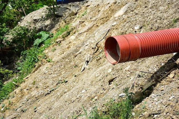 쓰레기 더미의 배경에 대해 빨간색 플라스틱 하수관에서 얇은 물줄기가 흐릅니다. 왼쪽에 텍스트를 위한 빈 공간이 많이 있습니다.