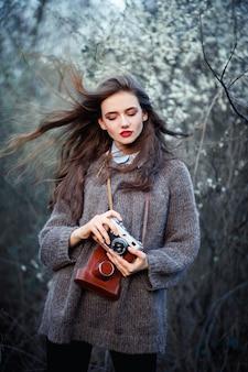 Худенькая молодая девушка в теплом сером свитере держит в руках старый винтажный пленочный фотоаппарат на фоне зеленых кустов и белых цветов в лесу