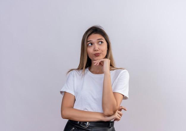 턱에 손을 유지하고 서있는 동안 멀리보고 흰색 티셔츠에 생각하는 젊은 여자