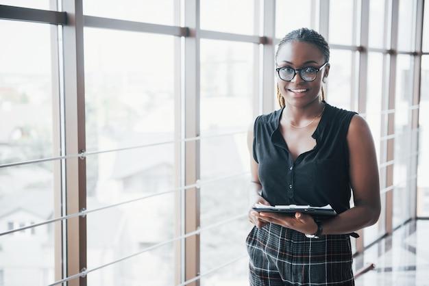 ドキュメントを保持している眼鏡をかけている思いやりのあるアフリカ系アメリカ人のビジネス女性。