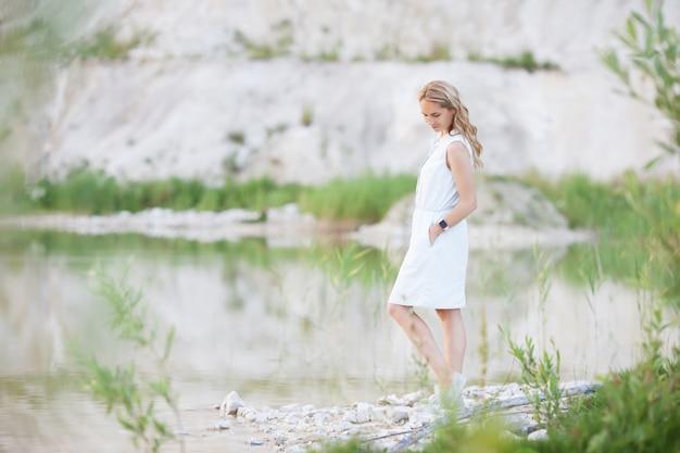 Задумчивая молодая женщина, стоящая на озере на фоне ярких песчаных холмов.