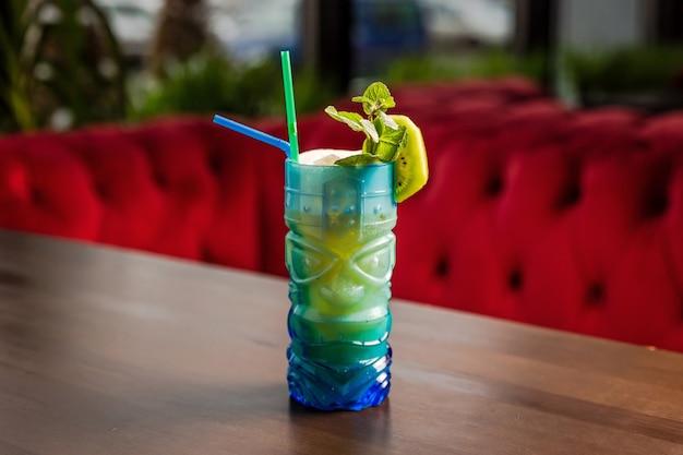Коктейль в стиле тики в ярком синем бокале с гарниром из киви и мяты в баре.